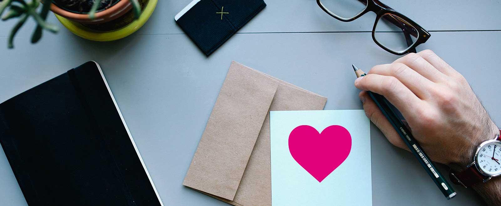 Schreibtisch von oben mit Schreibuntensilien und Herz